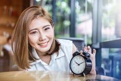 有闹钟的逗人喜爱的微笑的女孩在木桌上 免版税库存图片
