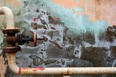 有阀门的有角度的金属管子对五颜六色的削皮墙壁在巴库,阿塞拜疆 库存图片