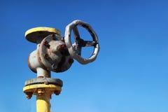 有阀门的老黄色煤气管在蓝天背景 免版税库存照片