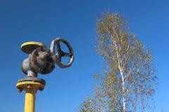 有阀门的老黄色煤气管在蓝天背景 图库摄影