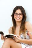 有阅读书的逗人喜爱的女孩。 库存图片