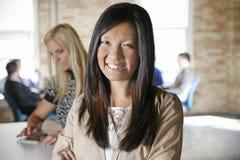 有队的亚裔女性女商人在现代办公室背景中 免版税库存照片