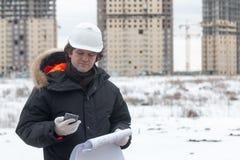 有防护安全帽的检查建筑图画的工程师或建筑师叫流动代课教师组在建筑 免版税库存图片
