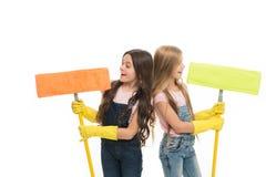 有防护手套的女孩和拖把准备好清洗 家庭责任 姐妹小的帮手 女孩逗人喜爱的孩子 免版税图库摄影