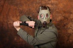 有防毒面具和katana剑的人在棕色蜡染布背景 库存图片