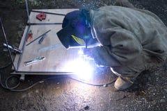 有防毒面具焊接金属的工作者在产业环境和火花传播 免版税库存照片