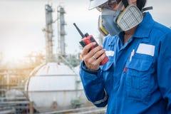 有防毒面具的技术员反对石油化工厂 免版税库存图片