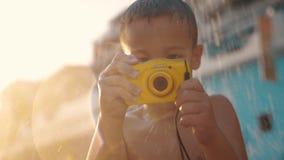 有防水照相机的孩子在海滩阵雨下 影视素材