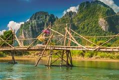 有阳伞的一名地方妇女在老挝过一座竹桥梁 库存照片
