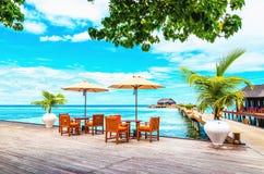 有阳伞的餐馆在反对海洋的天蓝色的水的一个木码头 免版税库存照片