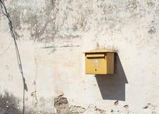 有阴影的偏僻的老邮箱在破旧的墙壁上 免版税库存图片
