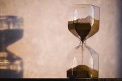 有阴影的滴漏在墙壁上 计时通过企业最后期限的,紧急概念和用尽时间 Sandglass 库存图片