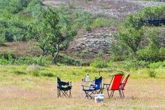 有阵营椅子和桌的露营地 免版税库存图片