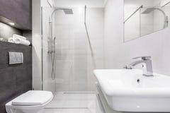 有阵雨的灰色和白色卫生间 免版税库存图片