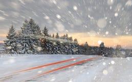 有阵雪的冬天路 采取与一张缓慢的快门速度,您看一辆通过的汽车的光 免版税库存照片