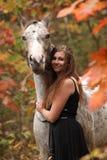 有阿帕卢萨马马的俏丽的妇女在秋天 免版税库存照片