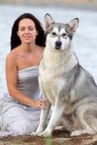 有阿拉斯加的爱斯基摩狗狗的少妇 库存照片