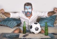 有阿根廷旗子的年轻有吸引力的人橄榄球支持者绘了面孔在庆祝vi的电视的愉快和激动的观看的杯子比赛 库存图片