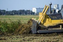 有附上grederom的黄色拖拉机做地面成水平 免版税库存照片