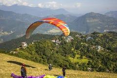 有降伞的几个滑翔伞在倾斜准备飞行,起飞的纵排奔跑反对绿色的背景 库存照片