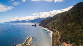 有陡峭的海岸和美丽的蓝色海洋天空的,马德拉岛,葡萄牙沿海路 免版税图库摄影