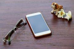 有陶瓷玩偶和镜片的巧妙的电话在木背景 免版税图库摄影