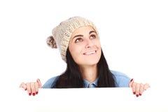 有隐藏在广告牌之后的帽子的十几岁的女孩 免版税库存照片