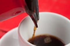有隔绝的加奶咖啡杯子在红色背景 图库摄影