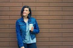 有隧道的少妇在蓝色牛仔裤夹克的耳朵 免版税库存图片