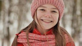 有雀斑的一个十几岁的女孩在她的面孔愉快地微笑入照相机 冬天森林风景的背景 表面 股票录像