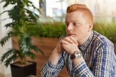 有雀斑的一个红头发人人在控制中结合在一起使手的衬衣穿戴了在坐在与绿色棕榈厕所的花盆附近的下巴 库存照片