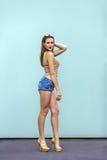 有雀斑的华美的深色的女孩在流行的服装的美好的构成:金鞋子、上面和小牛仔裤短裤 库存图片