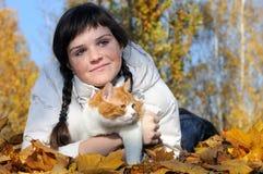 有雀斑的放松在公园的十几岁的女孩和猫 免版税库存图片