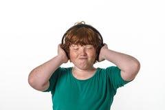 有雀斑的红头发男孩听的音乐。 免版税库存照片