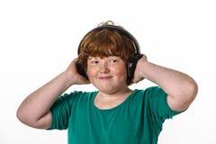 有雀斑的红头发男孩听的音乐。 免版税库存图片
