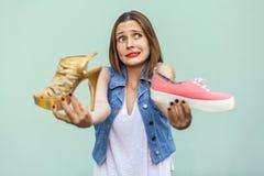 有雀斑的美丽的女孩在购物中心得到了选择运动鞋或英俊的鞋子,和看想出 库存照片