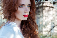 有雀斑的美丽的性感的红发女孩与在她的嘴唇近的开花的树的红色唇膏在城市在一个晴朗的晴天 库存图片