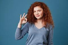 有雀斑的逗人喜爱的年轻红发女孩在显示好姿态用手的灰色衬衣,看秘密审议以愉快和 库存图片