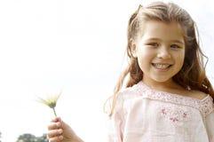 有雏菊的女孩在公园。 图库摄影
