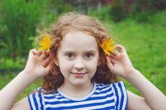 有雏菊的小女孩在耳朵在夏天公园 免版税库存照片