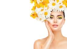 有雏菊的秀丽女孩开花接触她的皮肤的发型 免版税库存图片