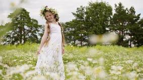 有雏菊花圈的青少年的女孩在她的头在有花的草甸走 股票录像