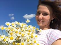 有雏菊花束的女孩在蓝天背景的 库存图片