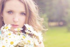 有雏菊花束的美丽的女孩与白发的在一个公园站立在一个晴朗的夏日 免版税库存照片