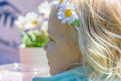 有雏菊头饰带的愉快的小女孩 免版税库存图片