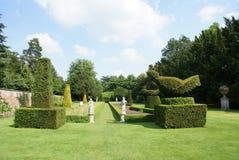 有雕象的正式赤柏松修剪的花园庭院在英国,欧洲 免版税库存照片