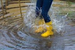 有雨靴的女孩跳进水坑 免版税库存图片