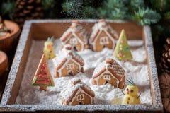 有雪人和树的逗人喜爱的圣诞节姜饼村庄 免版税图库摄影