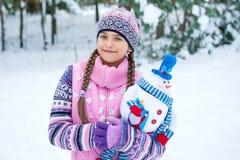 有雪人玩偶的愉快的冬天女孩 库存照片