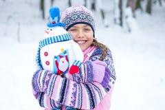 有雪人玩偶的愉快的冬天女孩 免版税库存照片